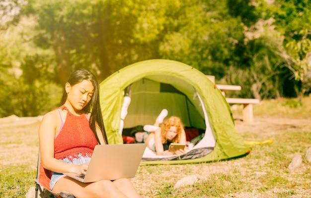 Mulheres, usando, gadgets, enquanto, acampamento