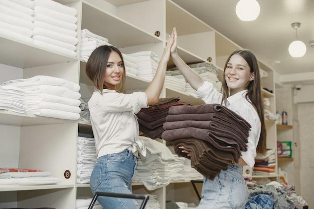 Mulheres usando máquina de secar. mulheres jovens prontas para secar roupas. conceito de processo interior, dryind.