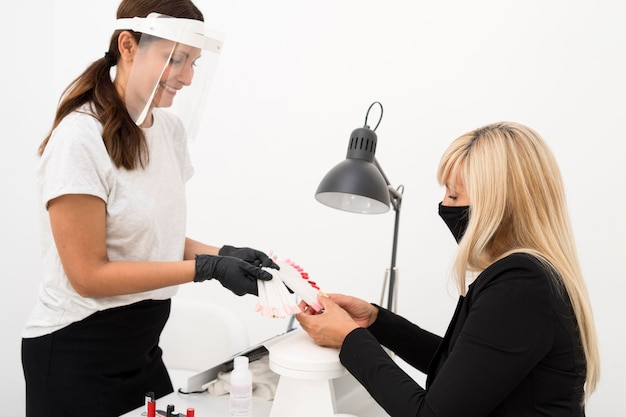 Mulheres usando máscara facial e escudo em salão de beleza