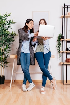 Mulheres usando o laptop enquanto trabalhadoras