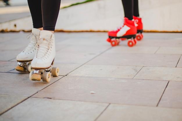 Mulheres usando rollerskates andando no pavimento