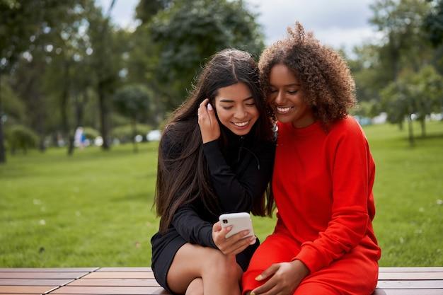 Mulheres usando smartphone ao ar livre