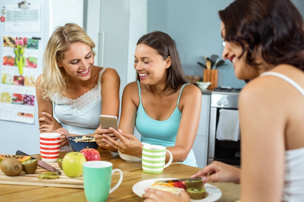 Mulheres usando telefone celular enquanto amigo tomando café da manhã na mesa