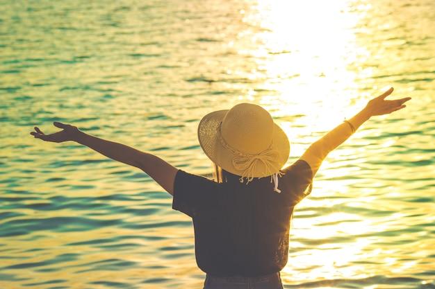 Mulheres usando um chapéu estão apreciando um belo pôr do sol na praia