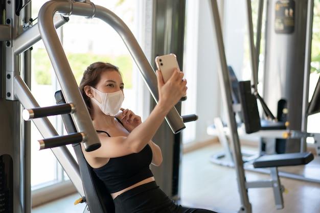 Mulheres vestindo máscara fazendo selfie em um telefone com câmera em roupas esportivas no ginásio.
