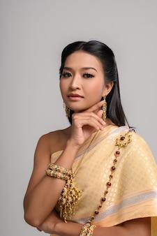 Mulheres vestindo roupas tailandesas e mãos tocando seus rostos