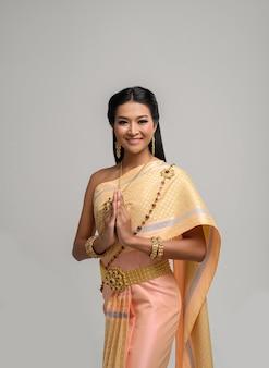 Mulheres vestindo roupas tailandesas que pagam respeito, símbolo sawasdee