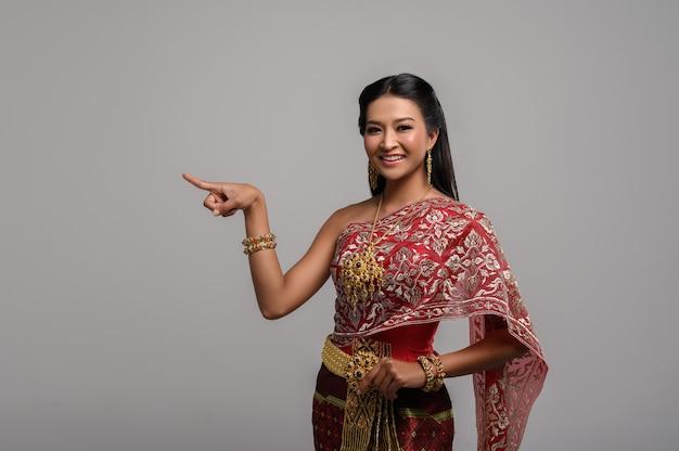 Mulheres vestindo trajes tailandeses que são simbólicos, apontando os dedos