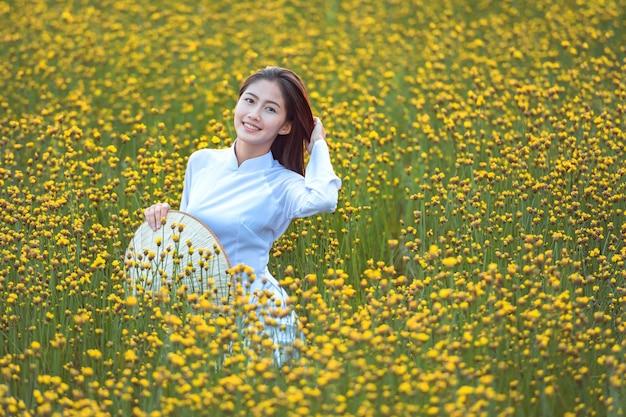 Mulheres vietnamitas em trajes tradicionais nacionais assistindo o jardim de flores amarelas