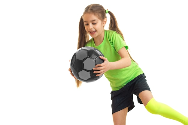 Mulherzinha feliz com uma bola de futebol multicolor nas mãos, isolado no branco