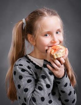Mulherzinha feliz comendo pão com manteiga com peixe em um fundo cinza