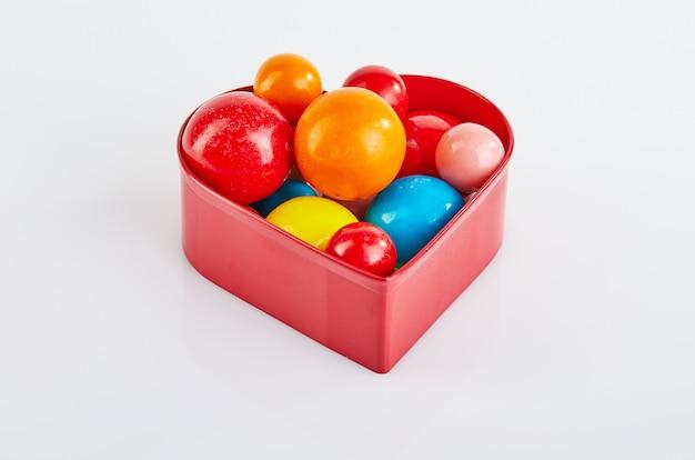 Multi bolas coloridas da pastilha elástica em um fundo branco em um coração vermelho com reflexão.
