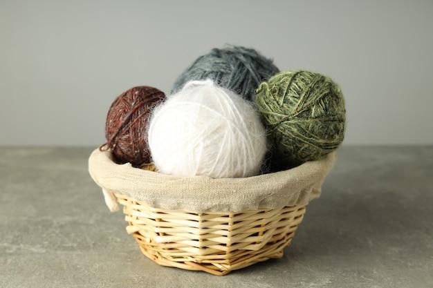 Multi bolas coloridas de lã em uma cesta de vime sobre um fundo cinza claro.