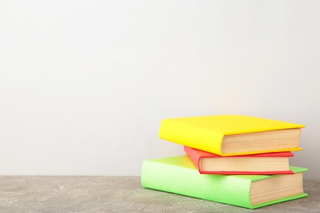 Multi colorido livros escolares na parede cinza