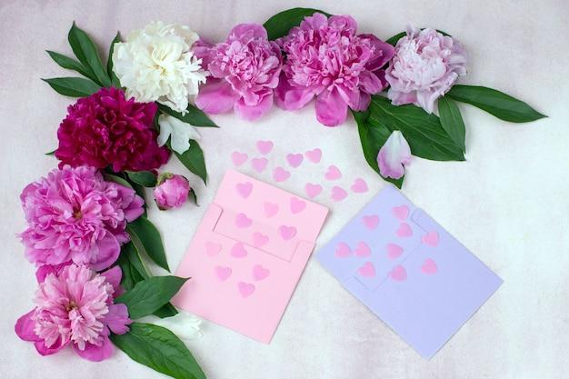 Multi colorido peônia brotos, dois envelopes e corações rosa