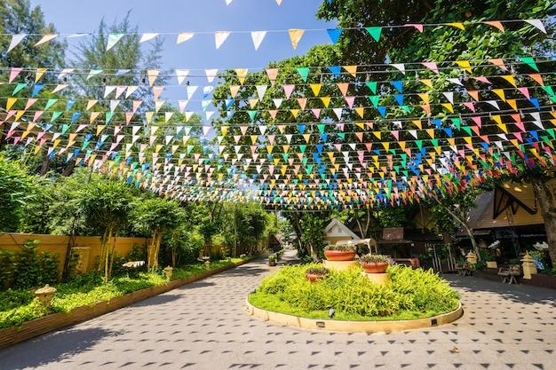 Multi colorido triangular sinalizadores pendurado no céu na estrada ao ar livre na festa de celebração