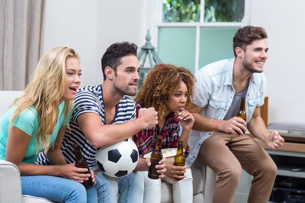 Multi étnica amigos assistindo jogo de futebol