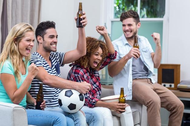 Multi étnica amigos com garrafa de cerveja, desfrutando de partida de futebol
