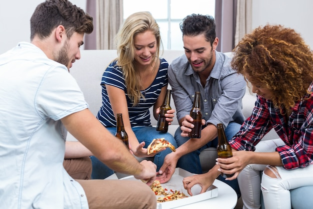 Multi étnica amigos desfrutando de cerveja e pizza