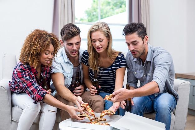 Multi étnica amigos segurando cerveja enquanto come pizza