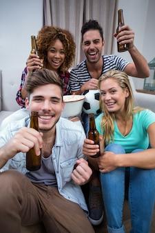 Multi étnica amigos torcendo enquanto assistia jogo de futebol