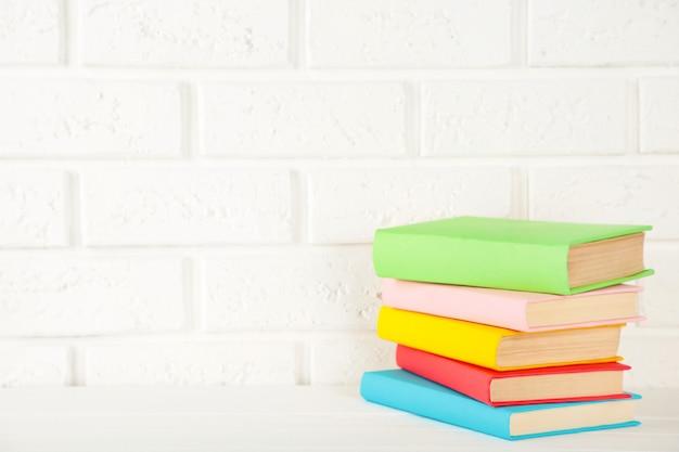 Multi livros de escola coloridos em um fundo branco com espaço da cópia.