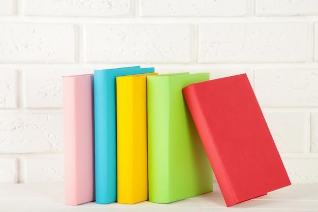 Multi livros de escola coloridos em um fundo branco.