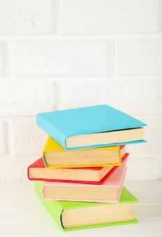 Multi livros escolares coloridos em uma parede branca com espaço da cópia.