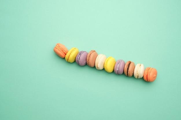 Multi macarons assados coloridos redondos com creme deitar em uma linha sobre uma superfície verde