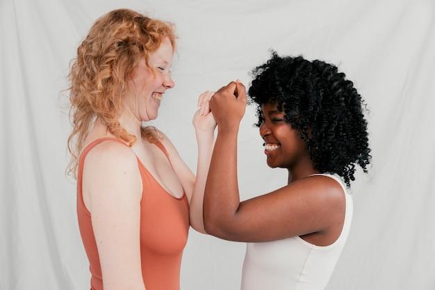 Multi mulheres novas étnicas alegres que tocam em suas mãos contra o contexto cinzento