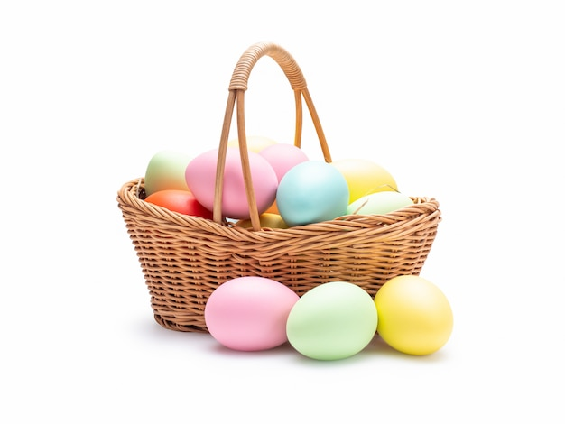 Multi ovos da páscoa das cores na cesta tecida isolada na parede branca com trajeto de grampeamento.