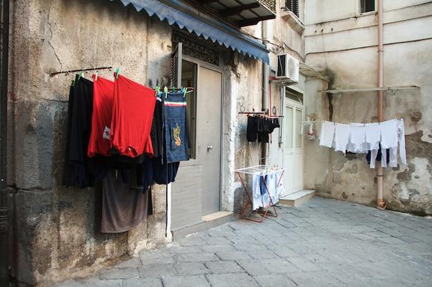 Multicoloridas roupas lavadas são secas na varanda no beco de nápoles