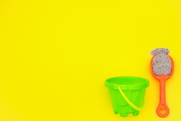 Multicolorido conjunto de brinquedos infantis para jogos de verão na caixa de areia ou na areia da praia em fundo amarelo