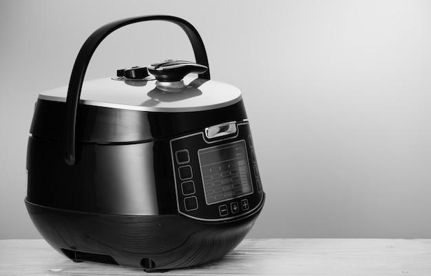 Multicooker moderno poderoso na tabela de madeira branca.