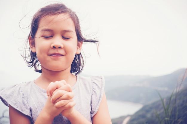 Multicultural menina asiática orando com as mãos fechadas na montanha, ao ar livre ventoso