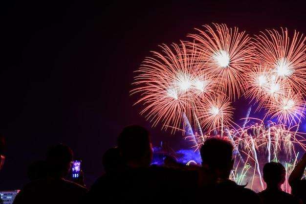 Multidão assistindo fogos de artifício e comemorando a cidade fundada.