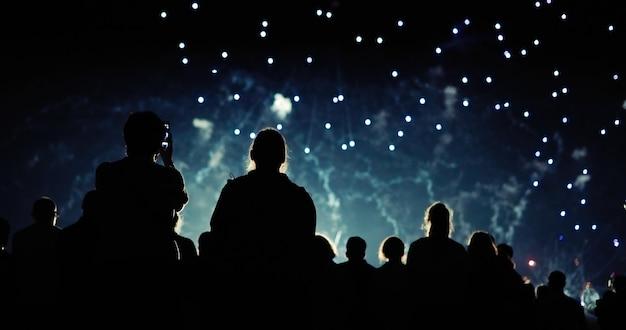 Multidão assistindo fogos de artifício e comemorando à noite