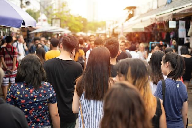 Multidão de pessoas anônimas andando no mercado de fim de semana.