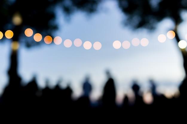 Multidão de pessoas ao ar livre esperando o pôr do sol