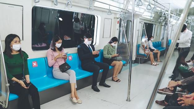 Multidão de pessoas usando máscara em uma viagem lotada de trem público de metrô