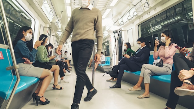Multidão de pessoas usando máscara em uma viagem lotada de trem público