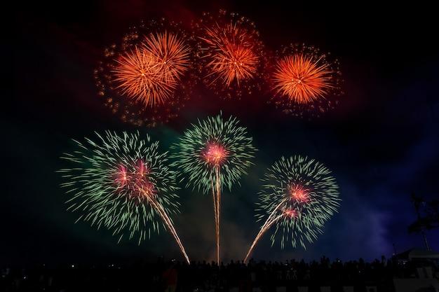 Multidão parece fogos de artifício de férias no céu escuro da noite.