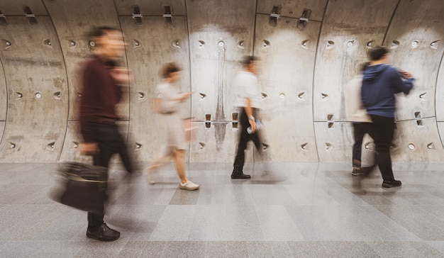Multidão turva de empresários irreconhecíveis andando no túnel do metrô moderno no dia de trabalho na hora do rush