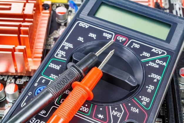 Multímetro digital com pontas de prova na placa-mãe do computador close-up