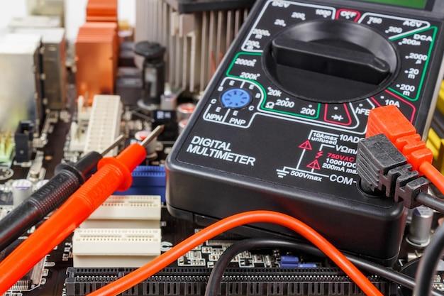 Multímetro digital com pontas de prova na superfície da placa-mãe closeup