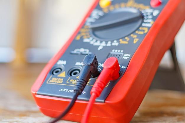 Multímetro digital com sondas conectadas na mesa de madeira