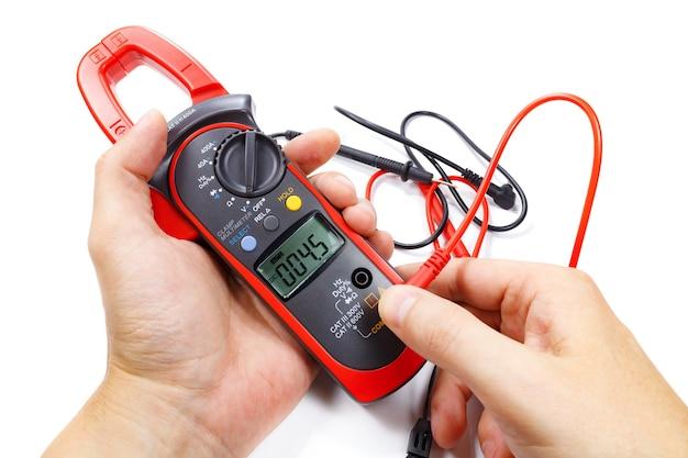 Multímetro digital de pinça com sondas na mão do homem no branco