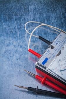 Multímetro do eletricista no conceito de construção de superfície metálica riscada.