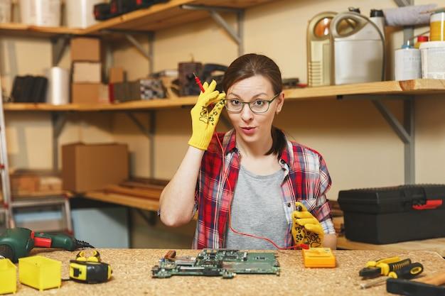 Multímetro para eletricista. bela jovem em luvas amarelas, óculos digital engenheiro eletrônico, reparando, soldando a placa-mãe do pc do computador na oficina na mesa de madeira com diferentes ferramentas.