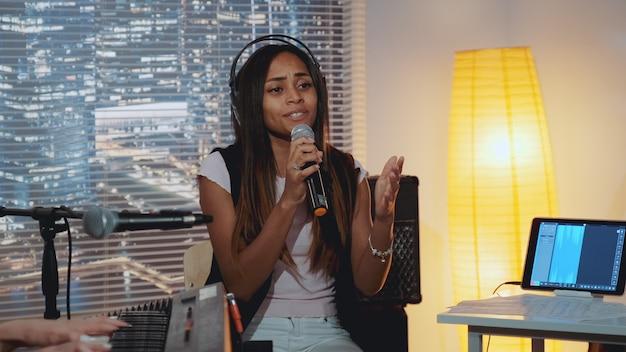 Multiracial bonita vocalista cantando música no microfone.